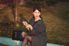 Het mooie maniermeisje schildert lippen in de straat Royalty-vrije Stock Afbeeldingen
