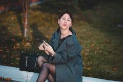 Het mooie maniermeisje schildert lippen in de straat Royalty-vrije Stock Afbeelding