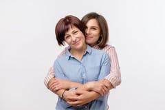Het mooie matureseniormamma en haar volwassen dochter koesteren, bekijken camera en glimlachen stock foto's