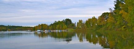 Het mooie meer van Minnesota met bezinning van jachthaven en boten stock afbeelding