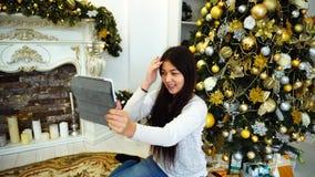 Het mooie Meisje in afwachting van Vakantie met Hulp van Inheemse Tablet wenst Nieuwjaar met Achtergrondkerstboom geluk stock footage