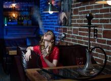 Het mooie meisje in avondjurk rookt een waterpijp binnen de bar stock foto
