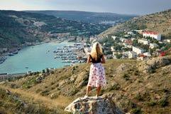 Het mooie meisje bekijkt het overzees en de overzeese stad De Krim, Balaclava, hoogste mening Actief levensstijlconcept royalty-vrije stock afbeelding