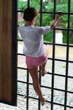 Het mooie meisje beklimt op een ijzerbar in een oude overspannen walkwa Stock Foto's