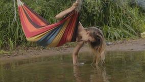 Het mooie meisje berijden in een hangmat over de rivier en het water raakt de hand stock footage