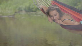 Het mooie meisje berijden in een hangmat over het water stock footage