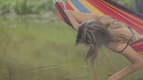Het mooie meisje berijden in een hangmat over het water stock video