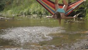 Het mooie meisje berijden in een hangmat over het water stock videobeelden