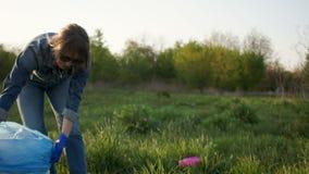 Het mooie meisje bij zonsondergang verzamelt afval in een grote plastic zak Ecologisch concept stock footage