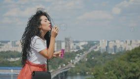 Het mooie meisje blaast bellen bij stadsachtergrond stock video