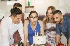 Het mooie meisje blaast de kaarsen van haar verjaardagscake met zijn vrienden royalty-vrije stock fotografie