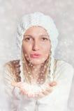 Het mooie meisje blaast sneeuwvlokken stock fotografie