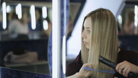 Het mooie meisje borstelt haar blonde haarzitting voor spiegel stock video