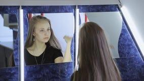 Het mooie meisje borstelt haar haar met de hand zittend voor spiegel stock footage