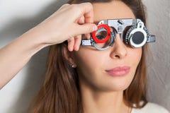 Het mooie meisje controleert visie in een oftalmoloog met correctief stock afbeelding