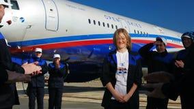 Het mooie meisje danst glimlachen en voelt schuw door collega's op vliegveld stock footage
