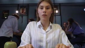 Het mooie meisje in de bibliotheek of in koffie drukt iets op de computer op de achtergrond van communicerende jongelui stock footage
