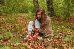 Het mooie meisje in de herfstbos houdt in haar handen gele bladeren Stock Fotografie