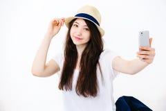 Het mooie meisje in de hoed maakt selfie op de vloer Stock Foto's