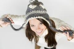 Het mooie meisje in de winter kleedt zich lookig omhoog met opgeheven wapens. Royalty-vrije Stock Afbeelding