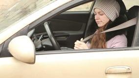 Het mooie meisje in de winterkleren zit in de auto stock video