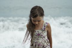 Het mooie meisje in de zomerkleding met nat haar bevindt zich zorgvuldig door het overzees stock fotografie