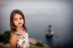 Het mooie meisje in de zomerkleding met nat haar bevindt zich zorgvuldig door het overzees stock afbeeldingen