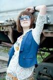 Het mooie meisje dichtbij een roestige spoorwegauto Stock Foto's