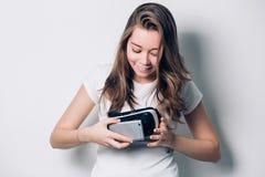 Het mooie meisje die een virtuele die werkelijkheidshoofdtelefoon houden, zet de telefoon, met een ernstig gezicht wordt teruggeg stock foto