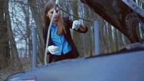Het mooie meisje die handschoenen dragen en controleert de hoeveelheid olie in de auto in 4K stock video