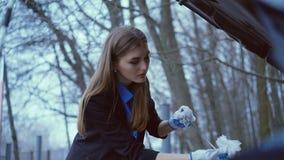 Het mooie meisje die handschoenen dragen en controleert de hoeveelheid olie in de auto in 4K stock footage