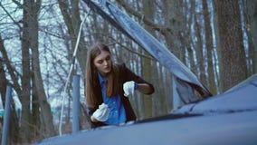 Het mooie meisje die handschoenen dragen en controleert de hoeveelheid olie in de auto in 4K stock videobeelden