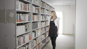 Het mooie meisje die van de blondestudent boek van plank in universitaire bibliotheek nemen stock video