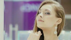 Het mooie meisje draagt juwelen in de badkamers stock videobeelden