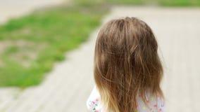 Het mooie meisje draait en onderzoekt de camera rond Donkerbruin, lang, omvangrijk haar Boeket van bloemen stock video