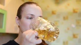 Het mooie meisje drinkt een groot glas bier stock footage