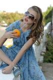 Het mooie meisje drinkt sap door een stro van een sinaasappel royalty-vrije stock foto's