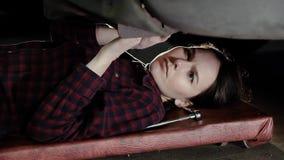 Het mooie meisje, een automobiele werktuigkundige, ligt onder de auto en draait de noten stock footage