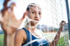 Het mooie meisje in een blauw overhemd in beenkappen is op het voetbalgebied wordt gehouden achter het net van de poort Redacties royalty-vrije stock foto