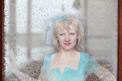 Mooi meisje in een blauwe kleding achter glas Stock Foto's
