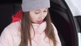 Het mooie meisje in een de winterbos kijkt door instagram, schudt haar hoofd stock footage