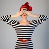 Het mooie meisje in een gestreepte kleding en een rode tulband op haar hoofd behandelt zijn ogen met handen en kijkt esoterisch t stock afbeelding