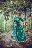 Het mooie meisje in een groene lange kleding bevindt zich op de tredentrapladder in het bos royalty-vrije stock afbeelding