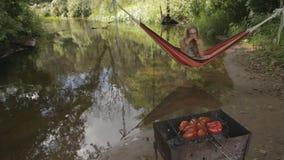 Het mooie meisje in een hangmat over het water eet graan stock footage