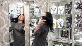 Het mooie meisje in een juwelenopslag kiest juwelen stock video