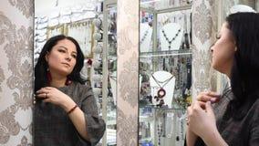 Het mooie meisje in een juwelenopslag kiest juwelen stock videobeelden
