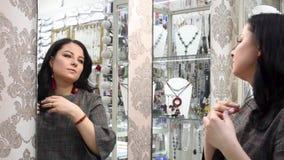 Het mooie meisje in een juwelenopslag kiest juwelen stock footage