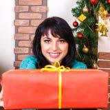 Het mooie meisje in een Kerstmisbinnenland geeft een rode giftdoos, loo stock afbeelding