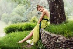 Het mooie meisje in een lange groene kleding bevindt zich blootvoets op het gras Royalty-vrije Stock Foto