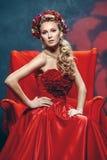 Het mooie meisje in een rode kleding Stock Foto